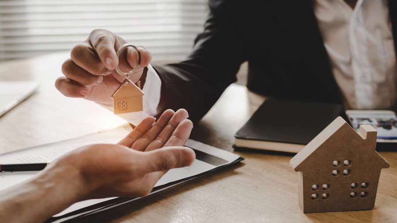 Real estate broker giving the key to a homeowner